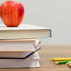 Apple on top of a stack of books on a desk