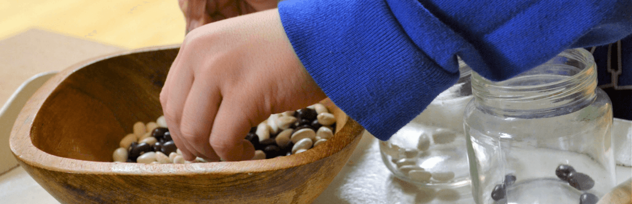 Child's hand reaching into a bowel with white and black dry beans in it
