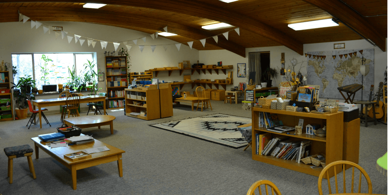 classroom with bookshelves, tables, and materials