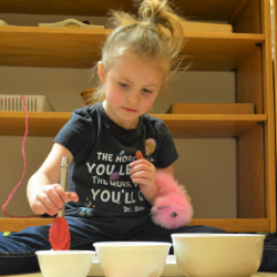 Child scooping materials into three bowls