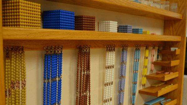 Shows the beads used to teach math skills organized in a wooden shelf